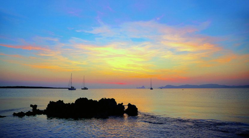 Ibiza sunset view from formentera Island with sailboat in Balearic Islands